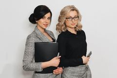 Two young successful girls in business suits with documents and mobile phone royalty free stock photography