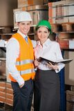 Two Young Supervisors At Warehouse. Portrait of two young supervisors with book standing at warehouse Stock Image