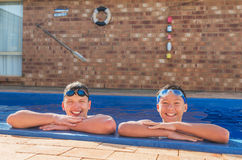Two young swimmers. Happy in their private inground pool Stock Images