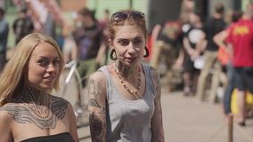 Two young tattoo girl walk on street. Talking to each other, look in camera Summer sunny day stock footage