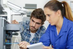 Two young technicians repairing printer. Fixing Royalty Free Stock Image