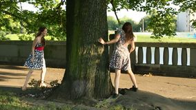 Two young  teen girls play indulge in the Park, run around the tree. Two young cute teen girls play indulge in the Park, run around the tree stock footage