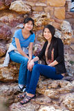 Two young teen girls sitting together on rocky stone seats Royalty Free Stock Photography