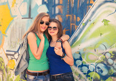 Two young teen hipster girl friends together having fun graffiti