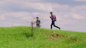 Two young teenage boys run along the green hill stock video footage