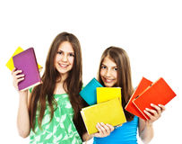 Two young teenage girls with colored books Royalty Free Stock Images