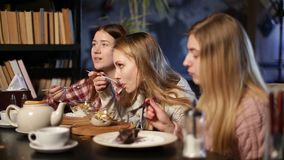Two young teenage girls eating desserts in cafe stock video footage