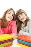 Two young teenage girls with pile colored book. Royalty Free Stock Image