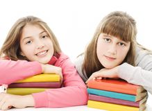 Two young teenage girls with pile colored book. Royalty Free Stock Photo