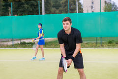 Two young tennis players playing doubles outdoors. Two young tennis players wearing a sportswear playing doubles at tennis court at early morning Royalty Free Stock Photo