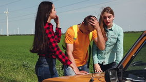 Two young tourist determine the route map and navigator. Three young visitors how to argue further movement route. The map on the hood of an old car stock video