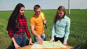 Two young tourist determine the route map and navigator. Three young visitors how to argue further movement route. The map on the hood of an old car stock footage