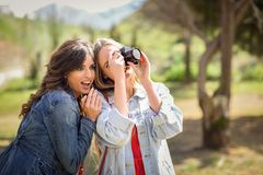 Two young tourist women taking photographs outdoors Royalty Free Stock Photos