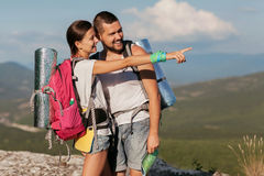 Two young tourists. With backpacks relaxing on rocks Stock Photography