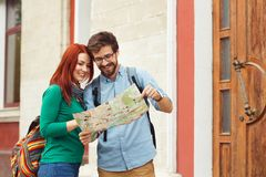 Two young tourists with backpacks sightseeing city. Travel concept. Hipster style people Stock Images