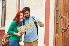 Two young tourists with backpacks sightseeing city. Travel concept. Hipster style people Royalty Free Stock Images