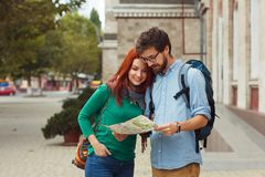 Two young tourists with backpacks sightseeing city. Travel concept. Hipster style people Stock Photography