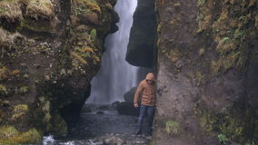 Two young tourists exploring the powerful waterfall Gljufrabui in Iceland. Man and woman in raincoat walking in rain. stock video