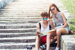 Two young tourists relaxing and examining a guide map Stock Photo