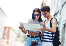 Two young tourists relaxing and examining a guide map. In a town royalty free stock photo
