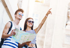 Two young tourists sightseeing a town, pointing with finger. Two young tourists sightseeing a city, holding a map, pointing with finger royalty free stock photo