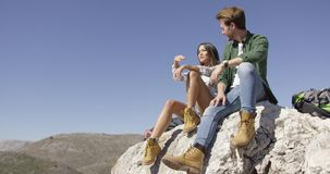 Two young tourists sitting on rock. Young couple sitting on huge rock and talking with beautiful mountain views on background stock footage
