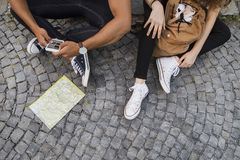 Two young tourists with smartphone in the old town. Unrecognizable two young tourists with smartphone and map in the old town. Teenagers sitting on the ground Royalty Free Stock Images