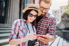 Two young tourists stand together and look on phone. They hold it together. Girl wears sunglasses. They are positive. stock image
