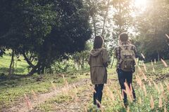Two Young Traveler with backpack, are holding map relaxing in gr. Eens jungle and enjoying with outdoor forest on background Summer vacations and Lifestyle Royalty Free Stock Image