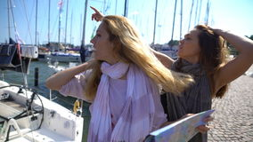 Two young traveler guided by a paper map on the city`s waterfront. Two women in an unfamiliar city. Two young traveler guided by a paper map on the city`s stock video