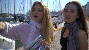 Two young traveler guided by a paper map on the city`s waterfront. Two women in an unfamiliar city. Two young traveler guided by a paper map on the city`s stock video footage