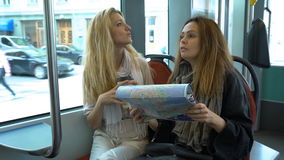 Two young traveler riding the tram in an unfamiliar city and use a paper map. stock video footage