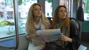Two young traveler riding the tram in an unfamiliar city and use a paper map. Two women in an unfamiliar city. Two young traveler riding the tram in an stock footage