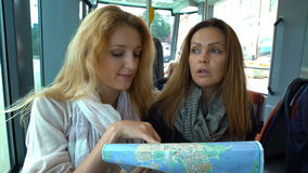 Two young traveler riding the tram in an unfamiliar city and use a paper map. stock video