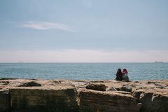 Two young Turkish girls in hijabs are sitting on the embankment talking and admiring the sea. Istanbul, Turkey royalty free stock photo