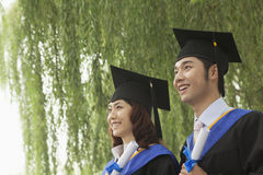 Two Young University Graduates Holding Diplomas And Looking Away Stock Photo
