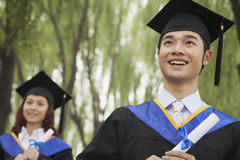 Two Young University Graduates Holding Diplomas, Man in Front Royalty Free Stock Images