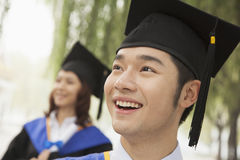 Two Young University Graduates Looking Away, Man in Front Stock Photo