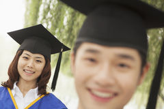 Two Young University Graduates Looking At The Camera, Man in Front Royalty Free Stock Images