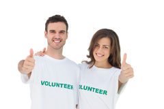 Two young volunteers giving thumbs up. On white background Royalty Free Stock Photos