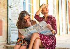 I think we are lost. Two young white Caucasian girls confused about where they are and where the go. Looking at a map stock images