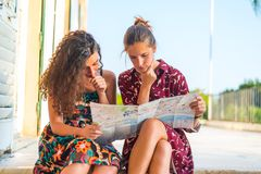 I think we are lost. Two young white Caucasian girls confused about where they are and where the go. Looking at a map royalty free stock images
