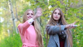 Two young white girl with long thick hair dancing in the autumn on the nature. Two beautiful happy girls with long hair in a coat happily dancing in the park stock footage