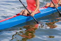 Two young woman athletes on rowing kayak on lake during competition stock photo