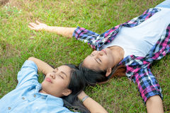 Two Young Woman ,Beautiful girl is relaxing lying on the grass i Royalty Free Stock Photography