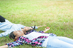Two Young Woman ,Beautiful girl is relaxing lying on the grass i Royalty Free Stock Photos