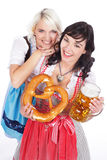 Two Young woman with beer glass. Two Young women with beer glass and bretzel in traditional costume stock image