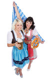 Two Young woman with beer glass. Two Young women with beer glass and bretzel in traditional costume royalty free stock photo