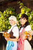 Two young woman with beer glasses and bretzel. Two young women with beer glasses and bretzel in traditional costume royalty free stock photos