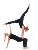 Two young woman in black show acrobatic exercise Stock Images